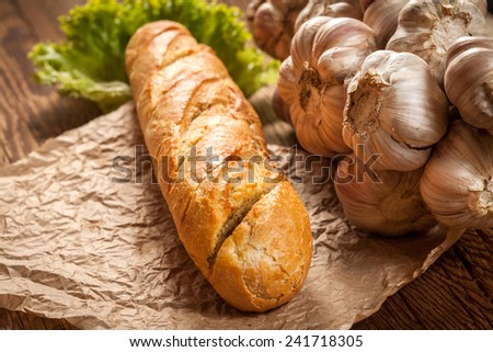 Garlic baguette with lettuce on a wooden table. - stock photo