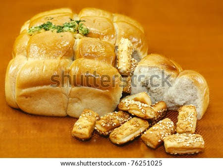 Garlic bread and biscuits on an orange background - stock photo