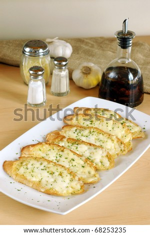 garlic bread  filled with herb butter on white plate - stock photo