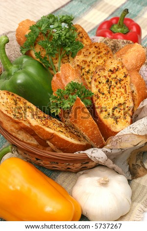 Garlic bread in a basket surrounded with colored peppers, garlic and parsley - stock photo