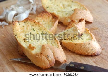 Garlic bread on wooden board - stock photo