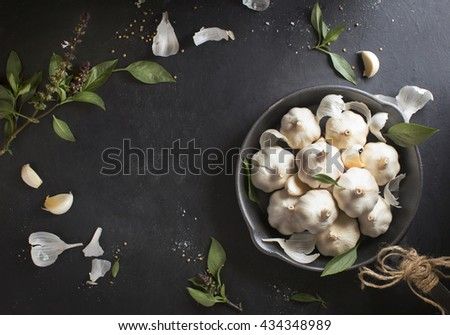 Garlic bulbs pile looking like a bouquet of flowers in black frying pan. Conceptual food still life image. Overhead view. - stock photo