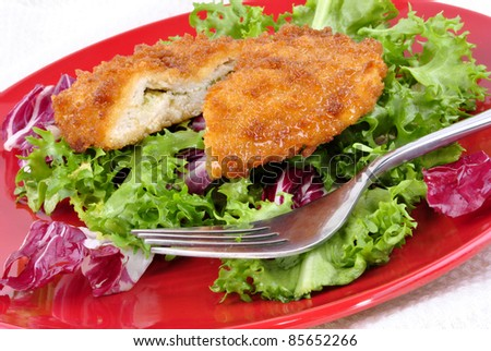 garlic chicken kiev with seasonal salad ready to eat and a fork - stock photo