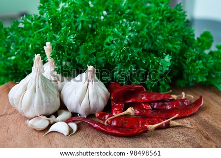 Garlic, chilli, parsley on wooden cutting board - stock photo