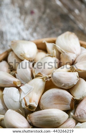 Garlic cloves in a bowl placed on wood flooring with copy space