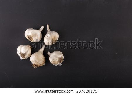 garlic cloves on dark chalkboard with copy-space - stock photo