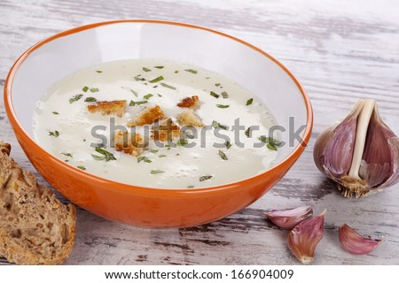 Garlic cream soup in orange bowl on white wooden background. Culinary healthy soup eating, rustic country style.  - stock photo
