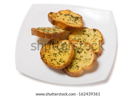 Garlic croutons drenched with herb butter isolated on white. - stock photo