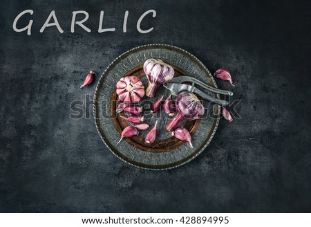Garlic. Fresh garlic. Red garlic. Garlic press. Violet garlic.Garlic background. garlic bulbs. Slate board. Wooden board. - stock photo