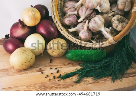 garlic in a basket, red and white onions, potatoes, cucumber and dill on a wooden background