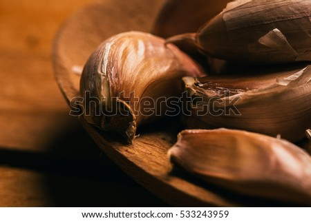Garlic in a wooden spoon on a light background.