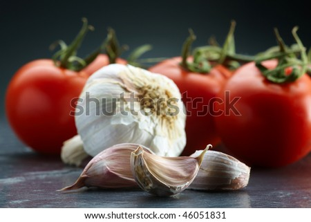 garlic in the foreground with blurred background tomatoes - stock photo