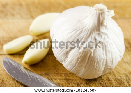 Garlic on a wooden chopping board. - stock photo