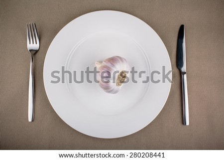 Garlic on white plate with fork and knife, top view
