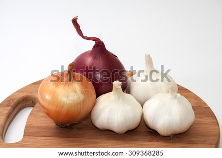 Garlic, onion and red onion on wooden kitchen board. - stock photo
