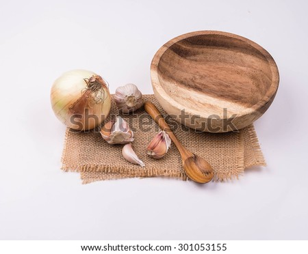 Garlic, onions, wood  cups, wooden spoons, put on sackcloth white background. - stock photo