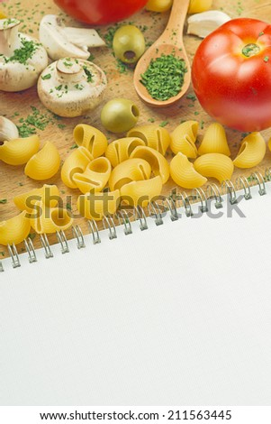 Garlic Parsley Mushroom Tomato Pasta Recipe Book on wooden board in the kitchen. Food preparation background. - stock photo