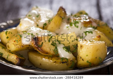 Garlic sauce (aioli) over baked potatoes with parsley on plate - stock photo