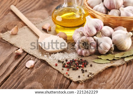 garlic, sea salt, pepper, sunflower oil, bay leaf, against a background of burlap and wooden planks - stock photo