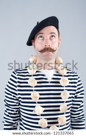 Garlic seller wearing necklace of garlic and French bretton top.  He's looking up and does not appear to be a happy person at the time the image was taken.  This is a three quarter length portrait - stock photo