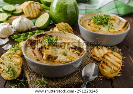 Garlic soup baked toast and cheese, cucumber-peas smoothie, bio organic food, little panini toasts - stock photo