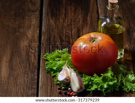 Garlic, tomato, salad and bottle of olive oil. Selective focus