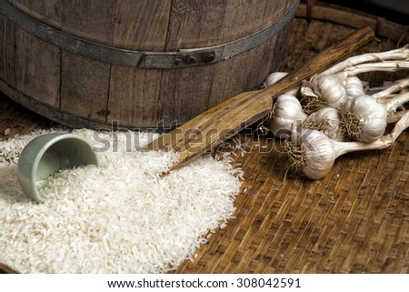 garlic, uncooked rice, on a wooden tray , still life - stock photo