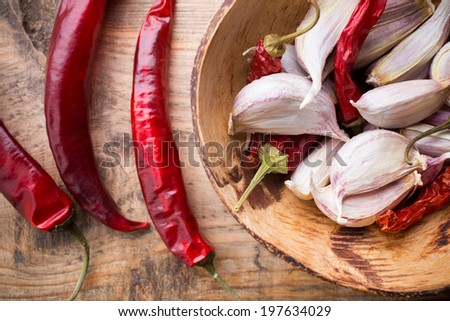 Garlic with red chili pepper on wooden background. - stock photo