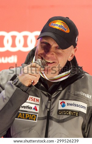 GARMISCH PARTENKIRCHEN, GERMANY. Feb 12 2011: Silver medal winner Didier Cuche (SUI) bites his medal at the medal ceremony for the men's downhill race at the 2011 Alpine skiing World Championships