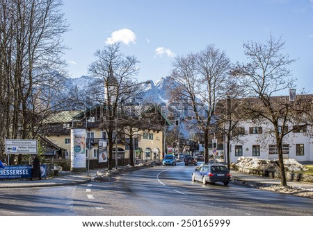 GARMISCH-PARTENKIRCHEN, GERMANY - JANUARY 10: small Alpine town street with traffic and typical houses, church and mountains at the backdrop in Garmisch-Partenkirchen, Bavarian Alps, January 10, 2015