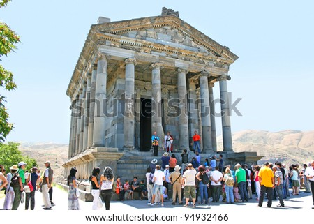 GARNI, ARMENIA - AUGUST 11, 2011: Unidentified tourists at fire ceremony in temple.Architectural complex established in 3rd century BC, combine Hellenistic elements.