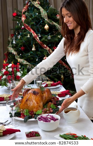 Garnished Christmas roasted turkey in young beautiful woman hands prepared for traditional family dinner with salad, fruits, vegetables, wine and champagne glasses on Christmas tree background - stock photo