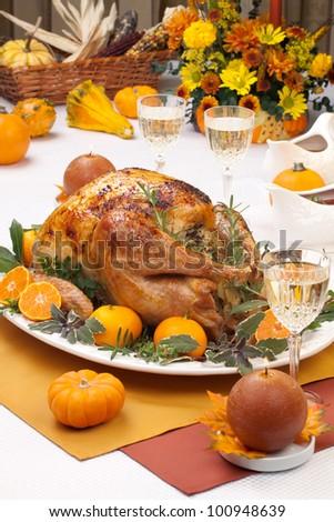 Garnished citrus glazed roasted turkey on holiday table, pumpkins, flowers, and white wine - stock photo