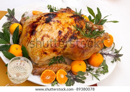 Garnished citrus glazed roasted turkey on holiday table, pumpkins, flowers, and white wine