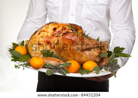 Garnished citrus glazed roasted turkey on platter is ready to be served - stock photo