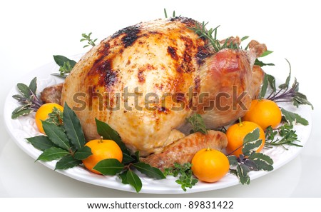 Garnished citrus glazed roasted turkey on tray over white background ...