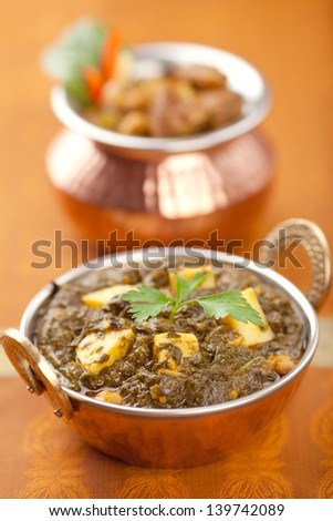 Garnished Palak Paneer in a copper bowl. - stock photo