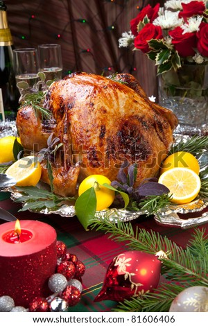 Garnished roast turkey on Christmas-decorated table with candles and flutes of champagne - stock photo