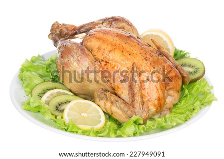 Garnished roasted thanksgiving chicken on a plate decorated with salad isolated on a white background
