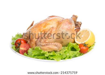 Garnished roasted thanksgiving chicken on a plate decorated with salad tomatoes lemon isolated on a white background