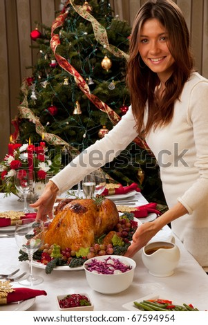 Garnished roasted turkey in young beautiful woman hands prepared for traditional family dinner decorated with salad, fruits, vegetables, vine and champagne glasses on Christmas tree background