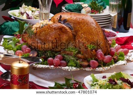 Garnished roasted turkey on Christmas decorated table with candles and flutes of champagne - stock photo