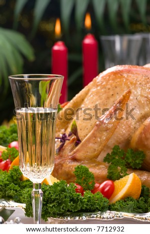Garnished roasted turkey on Christmas decorated table with candles and flutes of champagne. Shallow DOF. Focus on glass. - stock photo