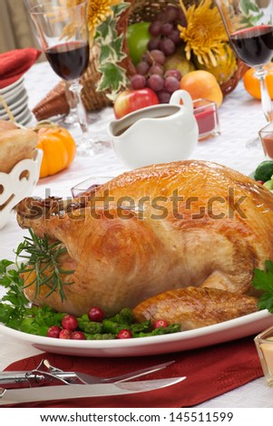 Garnished roasted turkey on fall festival decorated table with horn of plenty and red wine  - stock photo