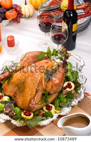 Garnished roasted turkey on holiday decorated table with candles and glasses of red wine