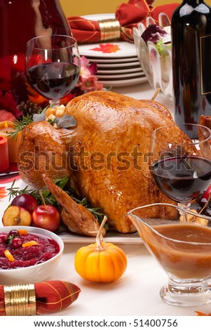 Garnished roasted turkey on holiday decorated table with pumpkins and glasses of red wine - stock photo