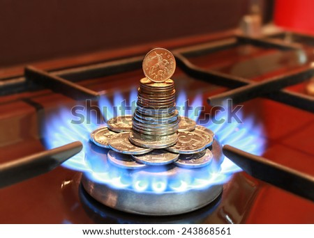 Gas burner with a blue flame and Russian coins - stock photo