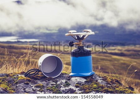 Gas camping stove and pot in the mountains - stock photo