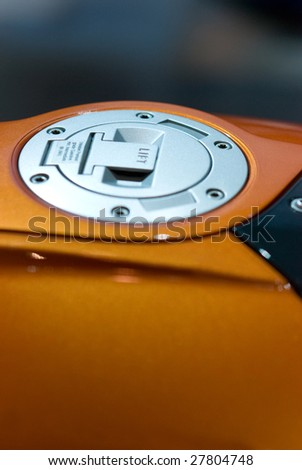 Gas cap of orange, large motorbike. Very shallow depth of field with focus around the center of the cap.
