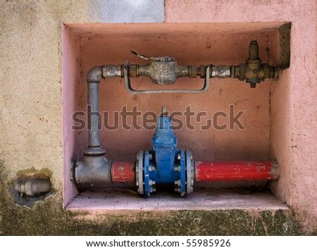 Gas device system in multicolored old wall - stock photo